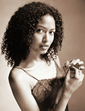 PORTRAIT OF YOUNG BLACK WOMAN WITH CURLY HAIR, HOLDING FLOWER SEPIA TO